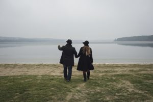 Romantic young couple approaching a lake